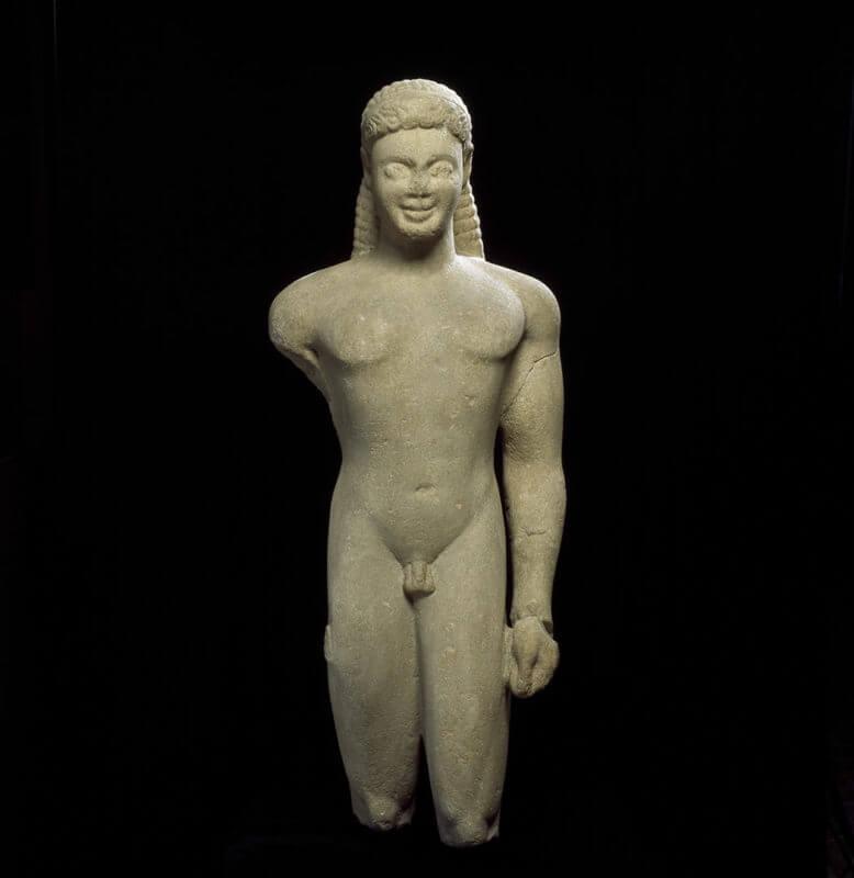 Statue fragmentaire d'un homme aux cheveux longs et souriant